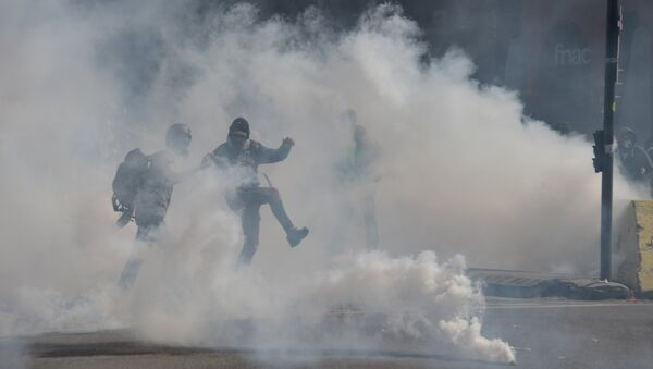 A protester throws back a tear gas canister during a demonstration called by the 'Yellow Vests' (gilets jaunes) movement, on April 13, 2019 in Toulouse. France has been rocked by months of weekly Saturday protests by the yellow vests, which emerged over fuel taxes before snowballing into a broad revolt against the French President. Pascal PAVANI / AFP - Sputnik France