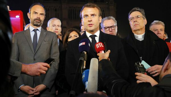 French President Emmanuel Macron (C) is accompanied by Mayor of Paris Anne Hidalgo (3L), French Prime Minister Edouard Philippe (L) French Culture Minister Franck Riester (2L) and Archbishop of Paris Michel Aupetit as he speaks at Notre-Dame Cathedral in Paris on April 15, 2019, after a fire engulfed the building. A fire broke out at the landmark Notre-Dame Cathedral in central Paris, potentially involving renovation works being carried out at the site, the fire service said.Images posted on social media showed flames and huge clouds of smoke billowing above the roof of the gothic cathedral, the most visited historic monument in Europe.  PHILIPPE WOJAZER / POOL / AFP - Sputnik France