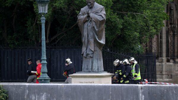 des sapeurs-pompiers près de la sculpture de Jean-Paul II après de l'incendie à Notre Dama de Paris - Sputnik France