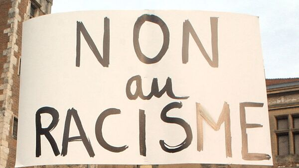 Une manifestante brandit une pancarte proclamant Non au racisme lors d'un rassemblement réunissant près de 500 personnes selon la police, le 08 janvier 2004 à Agen - Sputnik France