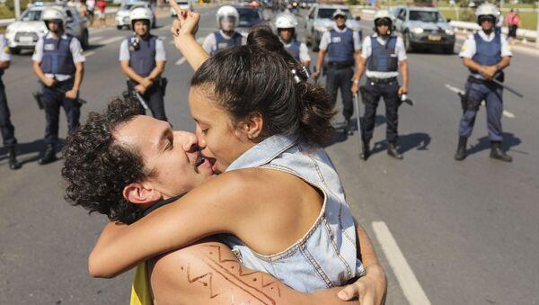Пара целуется напротив заслона полиции во время забастовки Национального союза студентов в Бразилии - Sputnik France