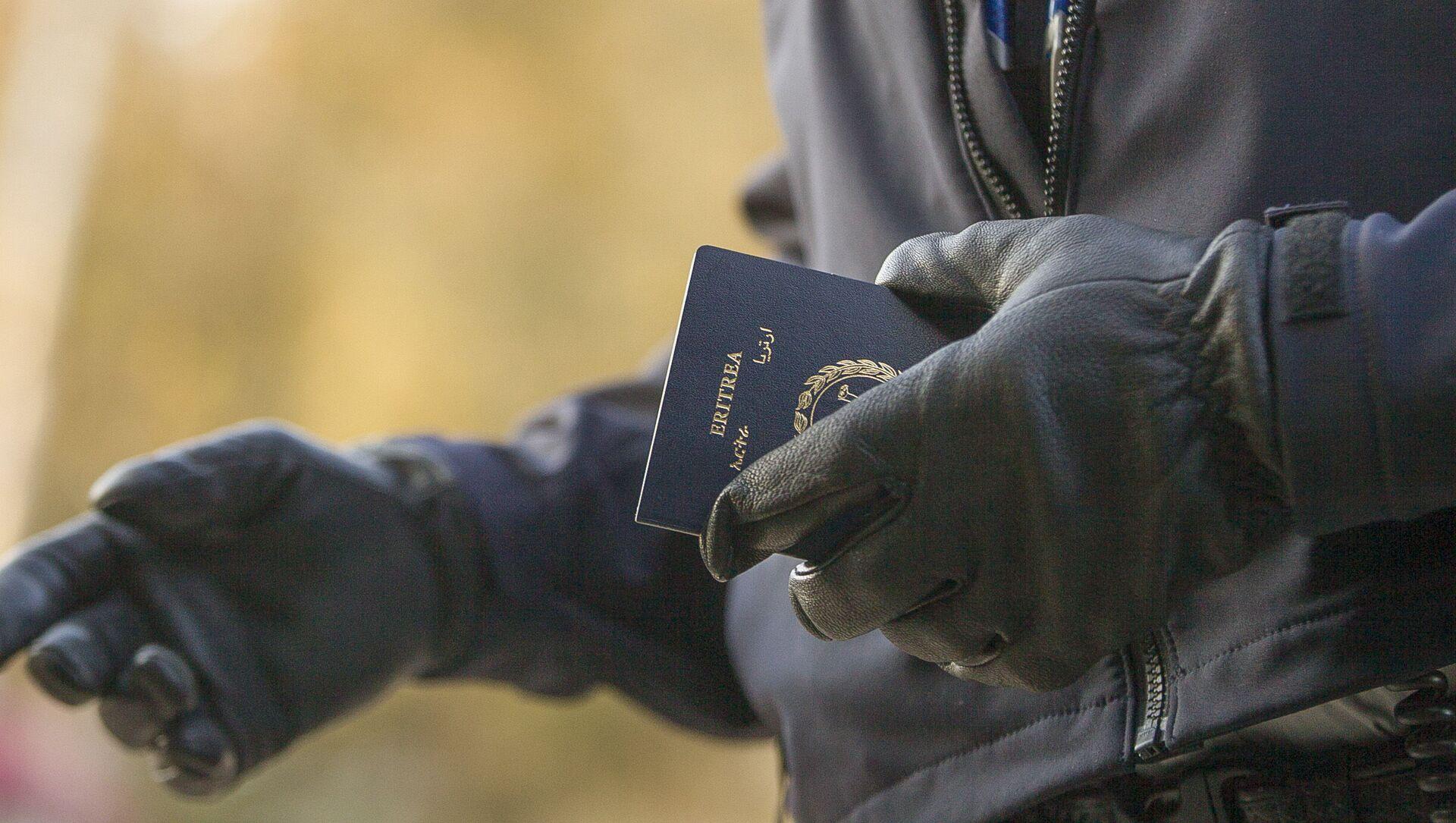 Un officier de la police aux frontières tient le passeport d'une femme érythréenne après son passage illégal de la frontière américano-canadienne - Sputnik France, 1920, 08.04.2021