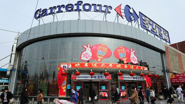 (FILES) In this file photo taken on January 27, 2011 a man carrying his bags of groceries steps out of a Carrefour store in Beijing. - The French retailer Carrefour announced on June 23, 2019 that it will sell 80% of its activities in China to the Chinese group Suning.com for a total of 620 million euros. (Photo by Frederic J. BROWN / AFP) - Sputnik France