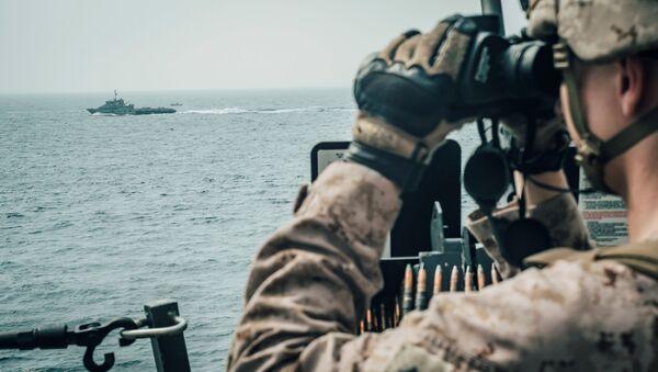Un militaire américain observe un vaisseau d'attaque rapide iranien du USS John P. Murtha pendant le transit du détroit d'Ormuz, dans la mer d'Oman au large d'Oman - Sputnik France