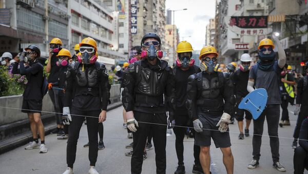 Protesters with protection gears face with riot policemen on a street during the anti-extradition bill protest in Hong Kong, Sunday, Aug. 11, 2019. Police fired tear gas late Sunday afternoon to try to disperse a demonstration in Hong Kong as protesters took over streets in two parts of the Asian financial capital, blocking traffic and setting up another night of likely showdowns with riot police. - Sputnik France