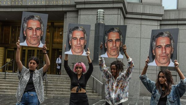 In this file photo taken on July 8, 2019, a protest group called Hot Mess hold up photos of Jeffrey Epstein in front of the Federal courthouse on July 8, 2019 in New York City. - Sputnik France