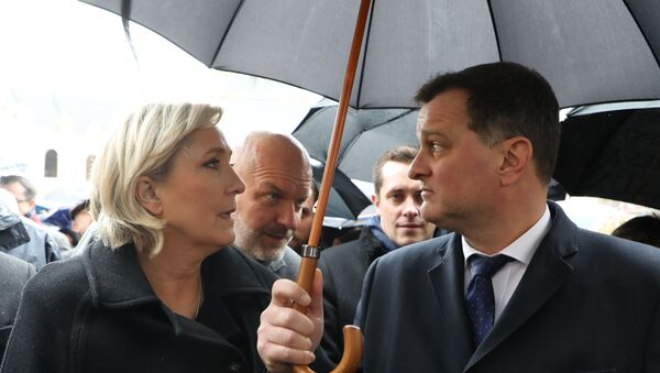 President of the French far-righ Front National (FN) party, Marine Le Pen (L), speaks to her companion, party Vice-President, Louis Aliot (R), next to her bodyguard Thierry Legier (2ndL) as they attend a national ceremony for Lieutenant-Colonel Arnaud Beltrame, on March 28, 2018 at the Hotel des Invalides in Paris. - France honours during a national ceremony on March 28 a heroic policeman who died offering himself as a hostage in a jihadist attack. Beltrame, 44, was the fourth and final victim in the shooting spree on March 23 in the southwestern towns of Carcassonne and nearby Trebes. (Photo by LUDOVIC MARIN / POOL / AFP) - Sputnik France
