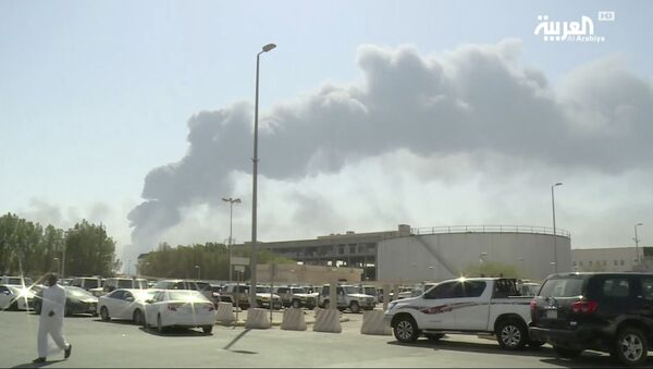 In this image made from a video broadcast on the Saudi-owned Al-Arabiya satellite news channel on Saturday, Sept. 14, 2019, a man walks through a parking lot as the smoke from a fire at the Abqaiq oil processing facility can be seen behind him in Buqyaq, Saudi Arabia. Drones launched by Yemen's Houthi rebels attacked the world's largest oil processing facility in Saudi Arabia and another major oilfield Saturday, sparking huge fires at a vulnerable chokepoint for global energy supplies - Sputnik France