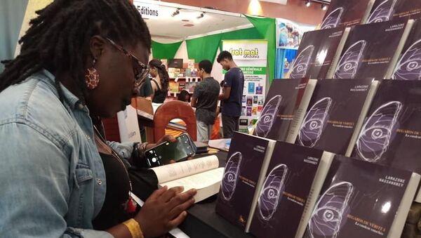 Une lectrice feuilletant le livre de Lamazone Wassawaney à l'édition 2019 du SILA à Abidjan  - Sputnik France