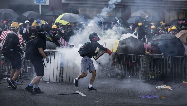 Protesters react among tear gas fired by police in the Sha Tin district of Hong Kong on October 1, 2019, as the city observes the National Day holiday to mark the 70th anniversary of communist China's founding - Sputnik France