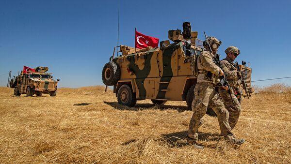 Les troupes américaines marchent près d'un véhicule militaire turc lors d'une patrouille conjointe dans un village syrien - Sputnik France