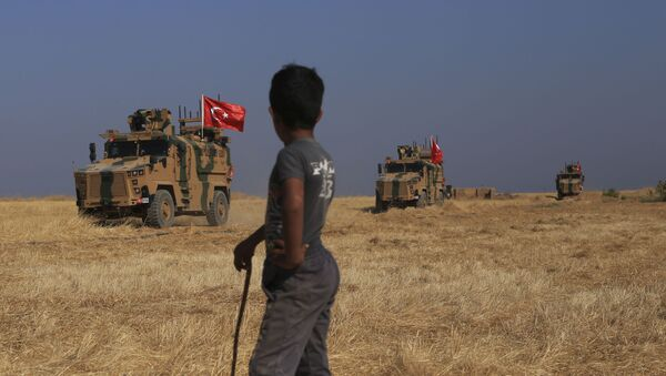 A Turkish n armored vehicles patrol as they conduct a joint ground patrol with American forces in the so-called safe zone on the Syrian side of the border with Turkey, near the town of Tal Abyad, northeastern Syria, Friday, Oct.4, 2019 - Sputnik France