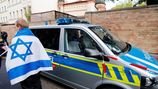 Un homme portant un drapeau israélien à côté d'un véhicule de police près de la synagogue de Halle - Sputnik France