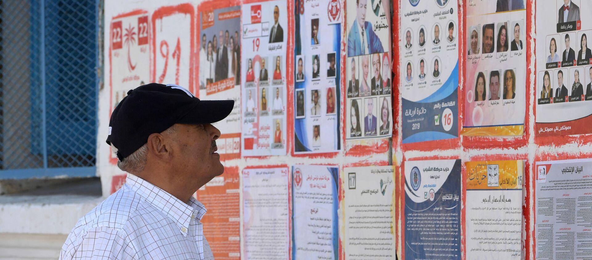 Un Tunisien devant les affiches des différents candidats aux législatives tunisiennes - Sputnik France, 1920, 18.10.2019