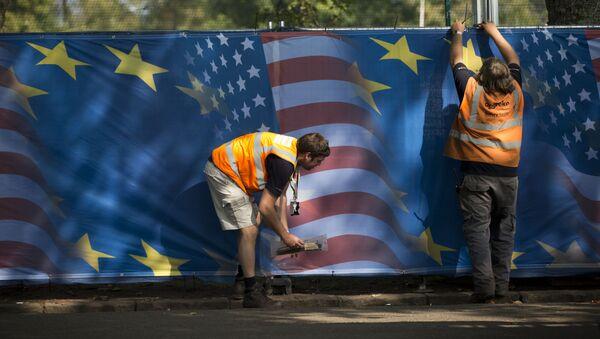 Des ouvriers accrochent des rideaux avec des motifs de drapeau américain et européen - Sputnik France