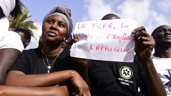 Un homme brandit une pancarte contre le franc CFA - Sputnik France