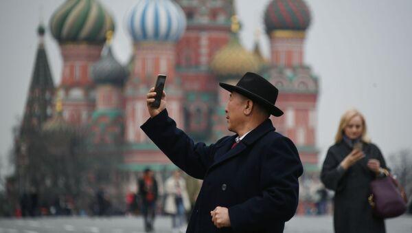 Турист фотографируется на Красной площади в Москве, на фоне храма Василия Блаженного - Sputnik France