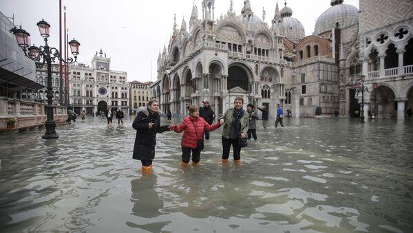 Des gens marchent dans l'eau sur la place Saint-Marc inondée à Venise, en Italie, le mercredi 13 novembre 2019 - Sputnik France