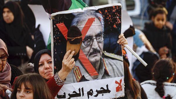 Une femme frappe avec sa chaussure le portrait de Khalifa Haftar lors d'une manifestation contre lui à Tripoli le 27 décembre 2019. - Sputnik France