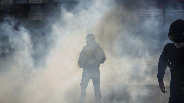 Des agents de la police couverts du gaz lacrymogène à Lyon. Photo d'archive  - Sputnik France