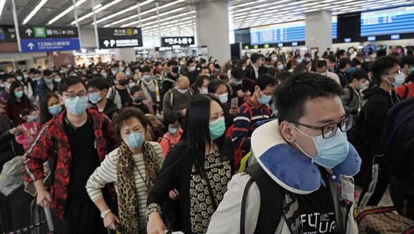 Passengers wear protective face masks at the departure hall of a high speed train station in Hong Kong - Sputnik France