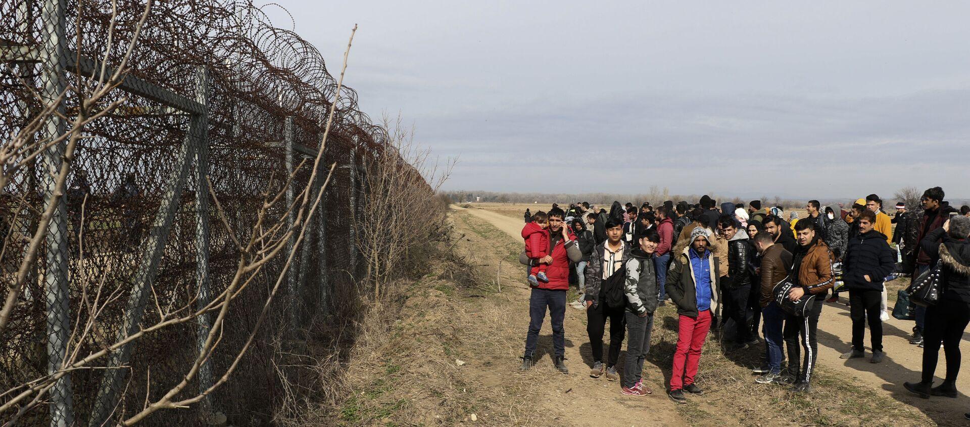 Des gardes-frontières grecs patrouillent, à gauche, alors que des migrants attendent à la frontière entre la Turquie et la Grèce, à Pazarkule, Edirne, en Turquie, le vendredi 28 février 2020. Les émissaires de l'OTAN tenaient des discussions d'urgence vendredi à la demande de la Turquie après le meurtre de 33 soldats turcs dans le nord-est de la Syrie, alors que des dizaines de migrants se sont rassemblés à la frontière turque avec la Grèce pour tenter d'entrer en Europe. (IHA via AP) - Sputnik France, 1920, 11.08.2021