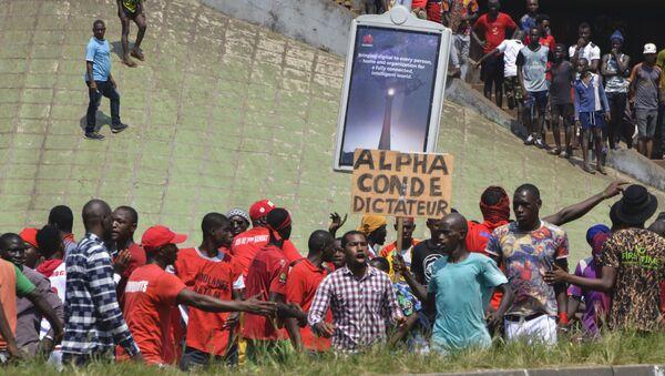 Un homme brandit une pancarte dénonçant la dictature d'Alpha Condé. - Sputnik France