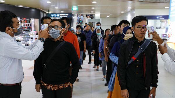 Los médicos miden la temperatura de los pasajeros debido al brote de coronavirus - Sputnik France