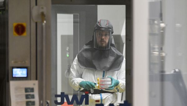 A virologist working on finding a treatment against COVID-19, the novel coronavirus, holds samples at a level 3 laboratory at the Rega Institute for Medical Research at the University of Leuven, on February 28, 2020. - The number of new coronavirus cases in the world rose to 83,853, including 2,873 deaths, across 56 countries and territories by 1300 GMT on February 28, 2020, according to a report gathered by AFP from official sources. (Photo by JOHN THYS / AFP) - Sputnik France