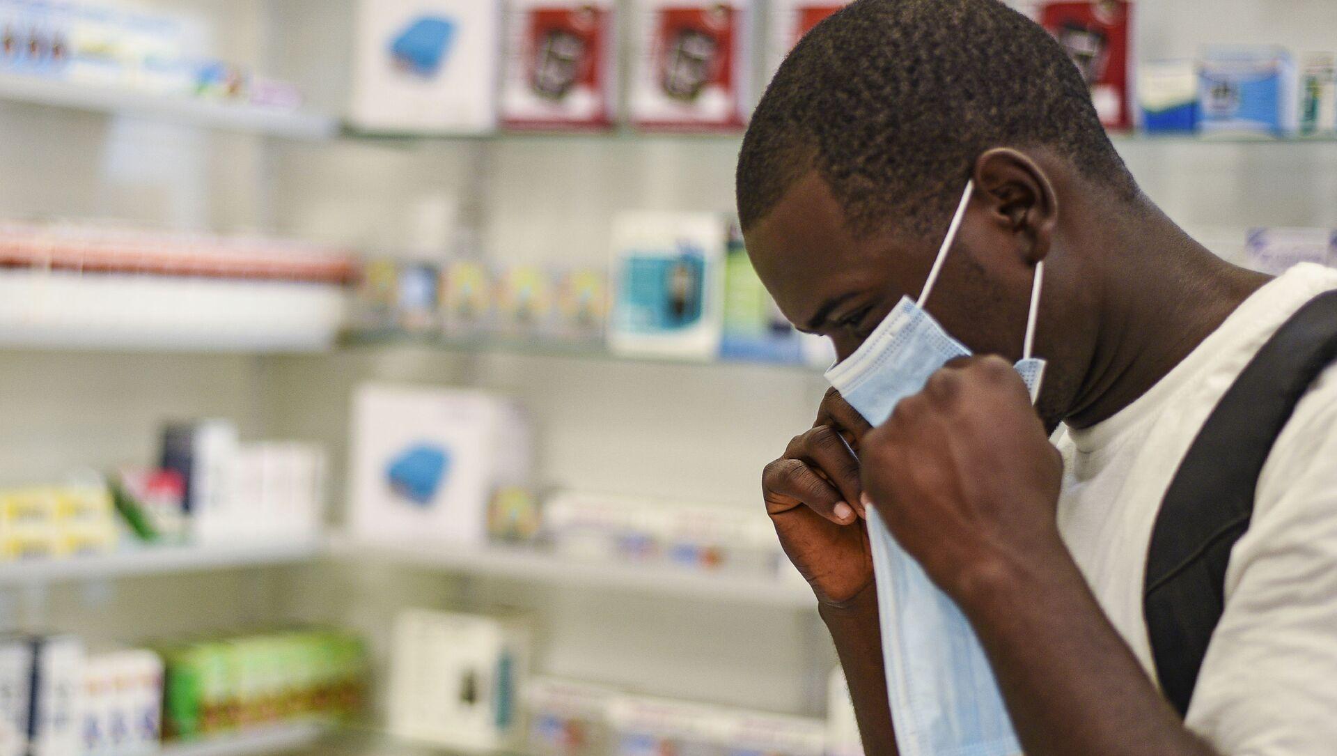 Un homme essaie un masque de protection, Zambie, février 2020. - Sputnik France, 1920, 09.09.2021