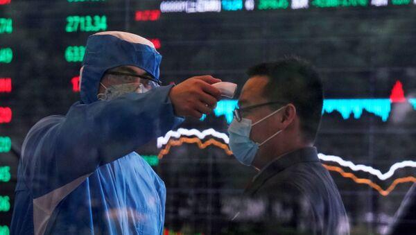 Un travailleur prend la température d'un homme à la Bourse de Shangaï - Sputnik France