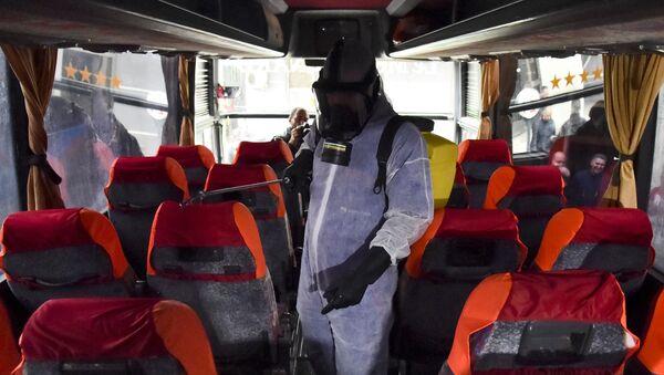 Un agent municipal désinfecte un bus contre le coronavirus à la station Kherrouba à Alger - Sputnik France