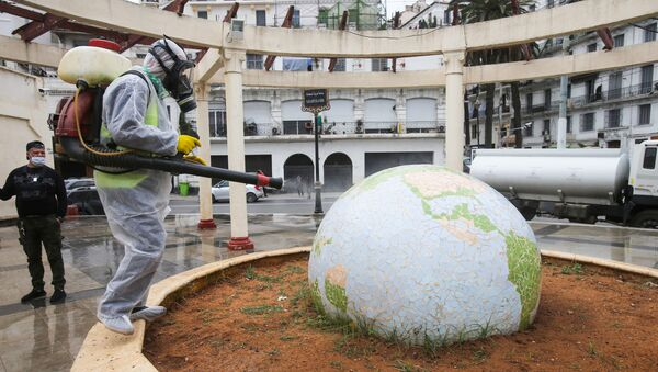 Un travailleur vêtu d'une combinaison de protection désinfecte une sculpture en forme de globe, à la suite de l'épidémie de coronavirus (COVID-19), à Alger, en Algérie, le 23 mars 2020. - Sputnik France