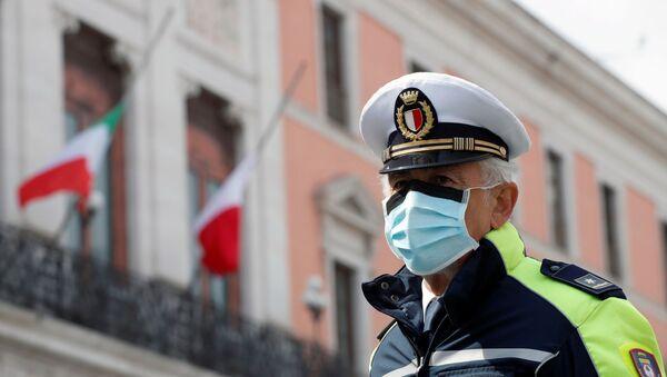 Un officier de police portant un masque de protection à Bari, en Italie - Sputnik France