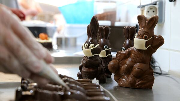 A chocolate maker finishes easter chocolate rabbits with a face mask on April 11, 2020 in Troyes amid the spread of the COVID-19 disease caused by the novel coronavirus. - Sputnik France