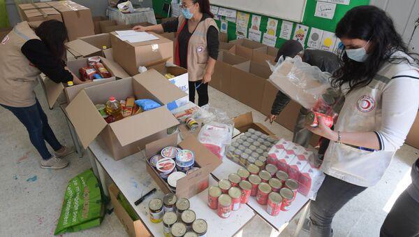 Préparation de cartons de l'aide alimentaire par des membres du Croissant rouge. - Sputnik France
