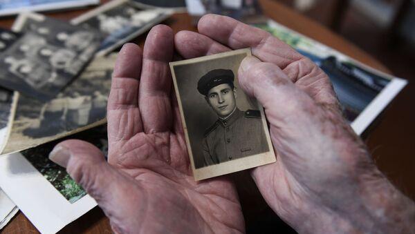 Le vétéran de la Grande guerre patriotique Alexeï Khavtourine regarde ses photos souvenirs  - Sputnik France