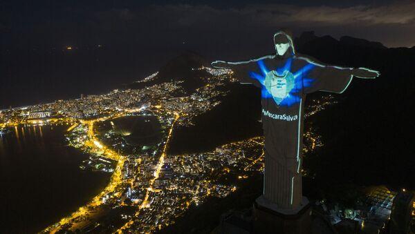 Статуя Христа-Искупителя с подсветкой в виде маски и надписью Маска спасает в Рио-де-Жанейро, Бразилия - Sputnik France