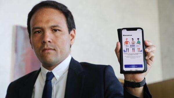Le secrétaire d'Etat au numérique Cédric O  tient en main un smartphone montrant l'application StopCovid - Sputnik France