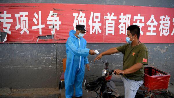 Le personnel de sécurité portant une combinaison de protection vérifie la température d'un homme sur une moto entrant sur le marché Xinfadi à Pékin, le 14 juin 2020 - Sputnik France