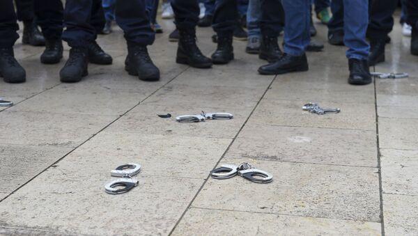 Des policiers français déposent symboliquement leurs menottes pour montrer leur colère. (Photo by NICOLAS TUCAT / AFP) - Sputnik France