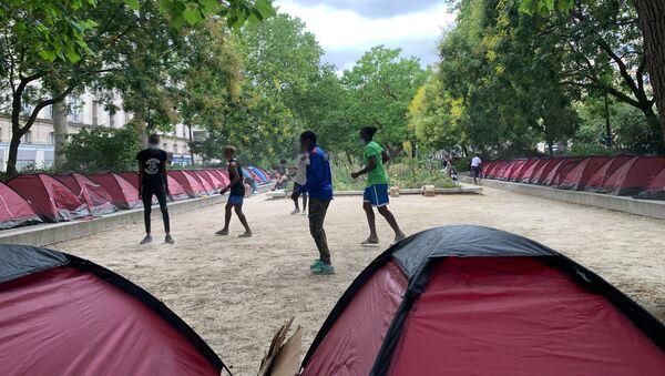 Des jeunes migrants jouent au football dans un parc parisien transformé en camp d'accueil  - Sputnik France