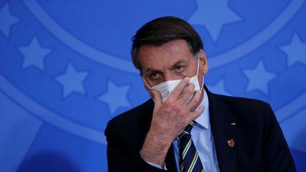 Le President Jair Bolsonaro ajuste un masque durant l'épidémie - Sputnik France