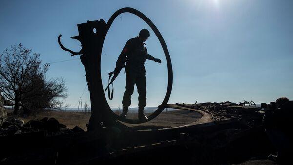 Боец ополчения ЛНР осматривает сгоревший украинский танк в поселке Новосветловка в Луганской области - Sputnik France