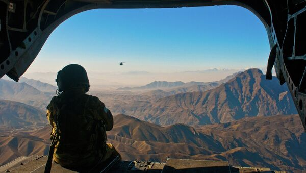 U.S. Army Spc. Devon Boxa, 7-158th Aviation Regiment, admires the Afghanistan landscape out the back door of her CH-47D Chinook helicopter as another Chinook follows - Sputnik France